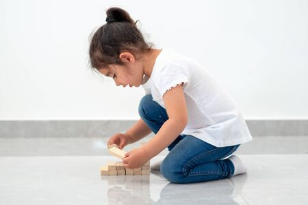 Cute child putting last block to the tower made of wooden blocks. Instilling leadership skills in children, development, education, growth,business success, early learning and achievement. Copy space.