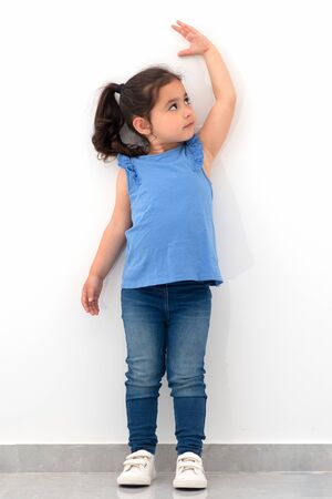 Beautiful little girl is measuring the growth on the background of wall. Funny child standing and raising left hand up.