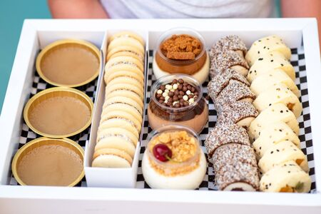 Delicious dessert chocolate and vanilla mousse decorated with sweet cream, cookies and candy in a glass jar. Fresh fruit sushi, alfajores, macaroons and creme brulee in white box.Happy hour, delivery. Zdjęcie Seryjne