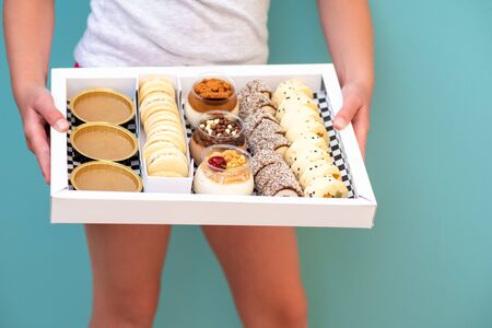 Young girl holding box with dessert chocolate and vanilla mousse decorated with sweet cream, cookies and candy in a glass jar, fruit sushi, alfajores, macaroons and creme brulee.