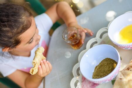 A small girl drinking tea and eating flatbread with olive oil and zaatar at home. Little kid enjoy the food and drink and have fun outdoors in backyard at sunny day. Archivio Fotografico