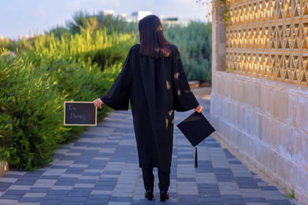 Rear view of graduating student standing against city background. College young woman student at Graduation Ceremony. Happy brunette multiple race girl in mortar boards and bachelor gowns outdoor.