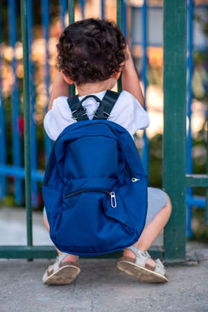 Back to School In the Time of Covid. Rear View Little Curly Schoolboy Ready For School.