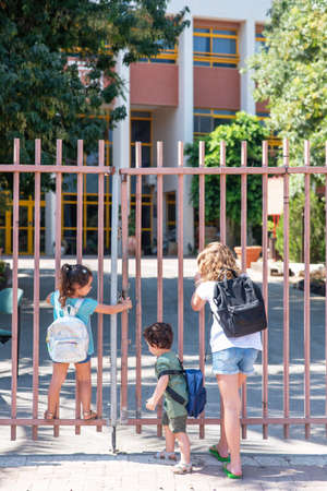 Little girls with blonde hair and black hair and toddler brother with curly hair stand and look through a closed metallic fence. Diverse school children going to school.
