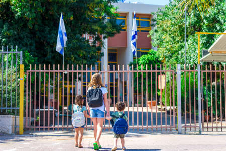 Happy diverse school children going to school outdoor at sunny day.Rear view of old sister and little girl and boy preschoolers with backpack go hand in hand to the kindergarten. Beginning of lessons. Reklamní fotografie