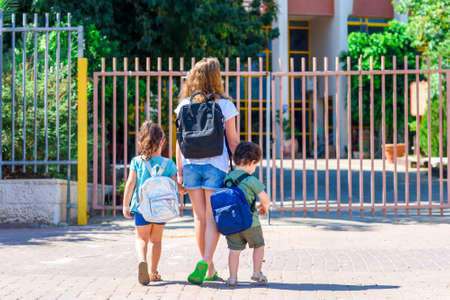 Happy diverse school children going to school outdoor at sunny day.Rear view of old sister and little girl and boy preschoolers with backpack go hand in hand to the kindergarten. Beginning of lessons.