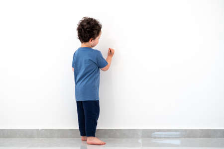 Curly cute little toddler boy painting with color pencil on the wall. Foto de archivo