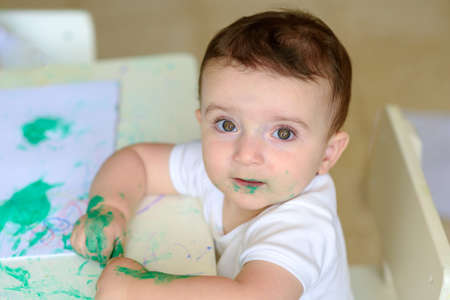 Cute adorable child painting at table. Portrait little baby drawing with green paint Reklamní fotografie