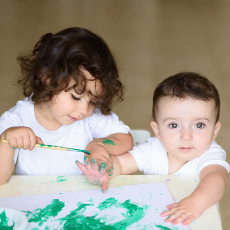 Cute little toddler girl and baby boy drawing with green watercolor paint and brush on hands. Curly adorable child , brunette kids painting at table.