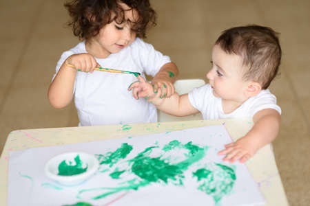 Cute little toddler girl and baby boy drawing with green watercolor paint and brush on hands. Curly adorable child , brunette kids painting at table. Reklamní fotografie
