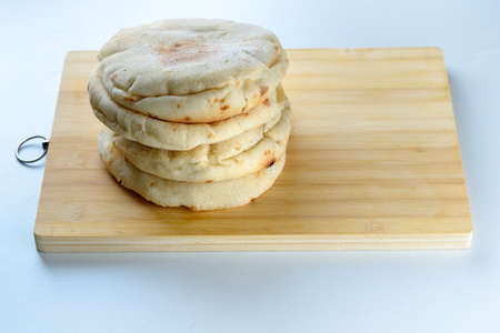 Stack freshly baked pittas on wooden board.Puffed freshly pita bread on white table.