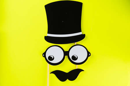 Top view image of funny masks glasses, hat and mustache on yellow background. Party, birthday, Halloween Father day, Purim, Fool day concept.