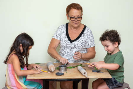 Grandmother with grandchildren applying green leaves using clay while doing arts and crafts. Digital Detox, happy family, hobbies, tech independence, healthy break concept.