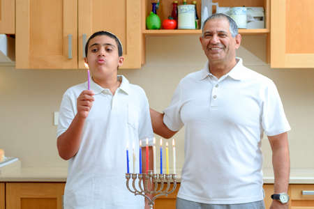 Happy family is lighting a candle celebrating together Jewish holiday Hanukkah. Jewish Dad and teenager son or grandfather with grandson lighting Chanukkah Candles in a menorah.Boy blowing candle.