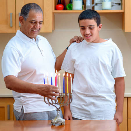 Happy family is lighting a candle celebrating together Jewish holiday Hanukkah. Jewish Dad and teenager son or grandfather with grandson lighting Chanukkah Candles in a menorah for the holdiay