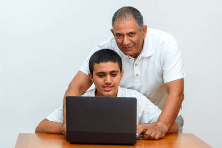Senior Father and teenage son using laptop. Boy and dad sitting at home working with tablet computer.Happy family old grandfather and grandson on laptop.Elderly teacher trainer and teen pupil boy. Banco de Imagens