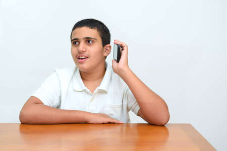 Teenager kid with mobile phone in hand sitting at wood table in home.Teen boy with deeper skin tones used his smartphone on white background in school.Young businessman talking on phone in office .