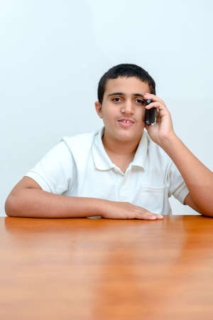Teenager kid with phone in hand sitting at wood table in home.Teen boy with mobile phone used his smartphone on white background in school.Young businessman in office .