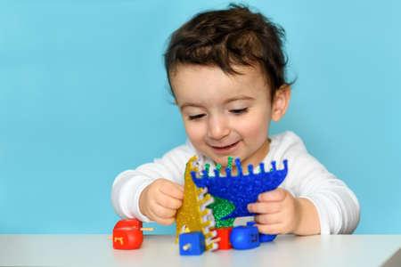 Jewish Boy Play With Festive Hanukkah Festive Hanukkah Blue Glitter Menorah And Colorful Wood Dreidels. Selective Focus.