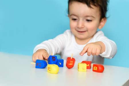 Little jewish boy playing with colorful wood dreidel. Selective focus on dreidel. Archivio Fotografico