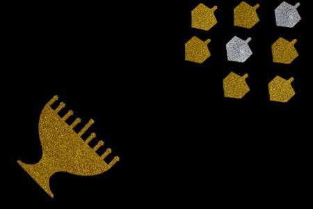 Golden glitter menorah and dreidel spinning top isolated on black. Image of Jewish holiday Hanukkah.