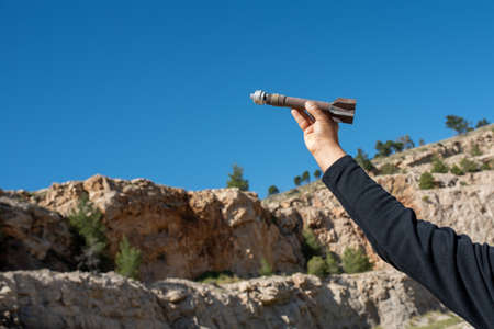 Mortar weapon bomb in man hands on nature background.