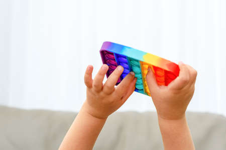 Close up child hands playing with the colorful pop It fidget. Soft focus.