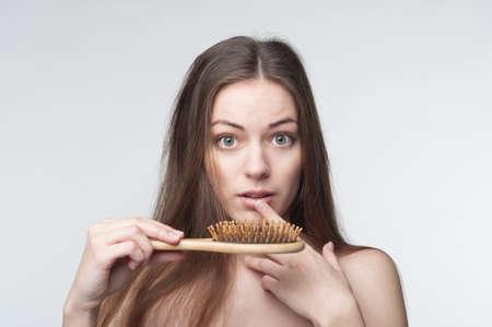 peineta: una joven y bella mujer olas a través de la pérdida de cabello Foto de archivo