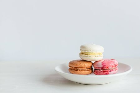 Three French macarons on a white plate. Multicolored macarons. Minimal concept, place for text.