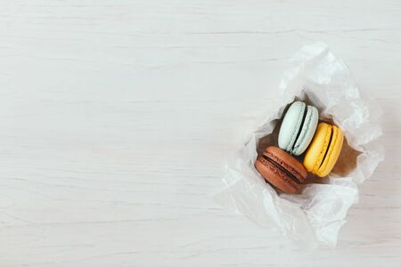 Three French macarons in gift box on a white wooden table. Chocolate, yellow and light blue macarons. Place for text.