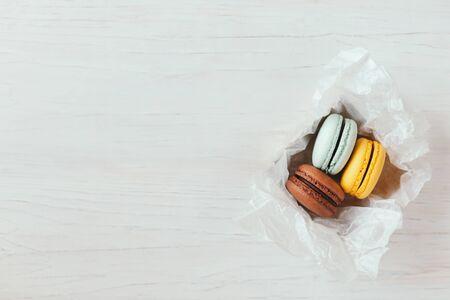 Tres macarons franceses en caja de regalo sobre una mesa de madera blanca. Macarons de chocolate, amarillo y celeste. Lugar para el texto. Foto de archivo