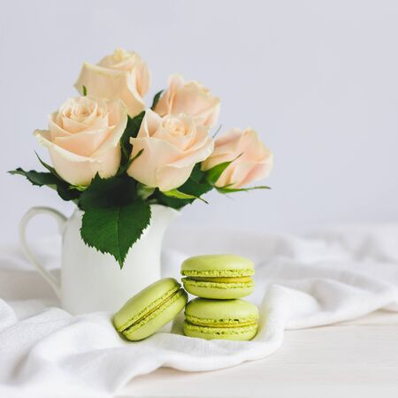 Two light green French macarons with tender roses in a vase on white background. Close up.  Pistachio macarons. Place for text. 스톡 콘텐츠
