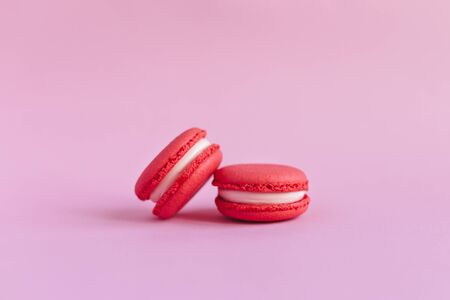 Two tasty french macarons on pink background.  Close-up. Place for text. 스톡 콘텐츠