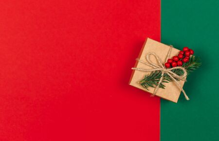 Craft gift box with spruce branch and red berries on green and red background. Holiday eco-friendly concept. Place for text. Flat lay. Reklamní fotografie