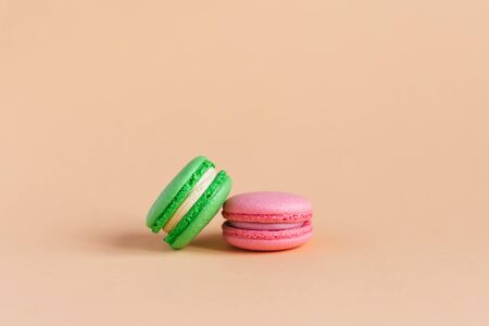 Two tasty french macarons on peach pastel background.  Pink and green macarons. Close-up. Place for text.