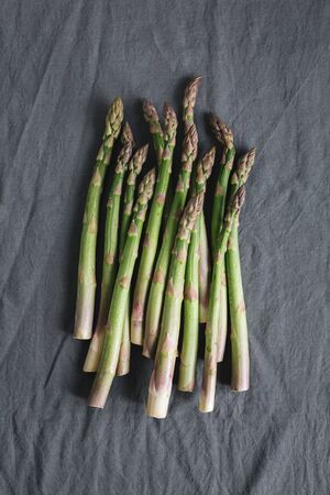 Bunch of  fresh asparagus on a grey linen cloth. Flat lay. Place for text.