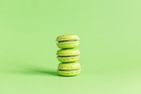 Tasty french macaroons on a light green pastel background. Place for text.