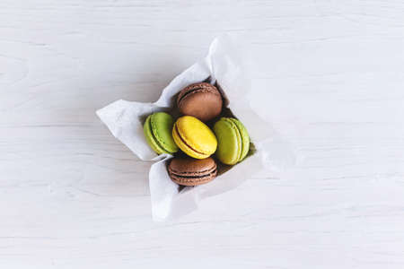 Tasty french macarons in a box on white wooden table. Place for text. Flat lay.