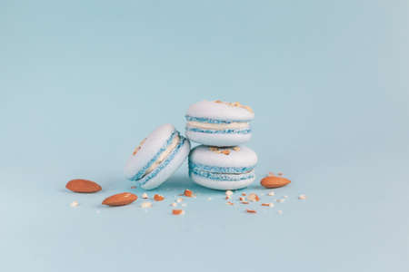 Tasty french macaroons with almond nuts on a light blue pastel background.  Place for text. 版權商用圖片