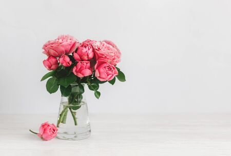 Romantic bouquet of pink roses in a glass vase on a white background.  Place for text.