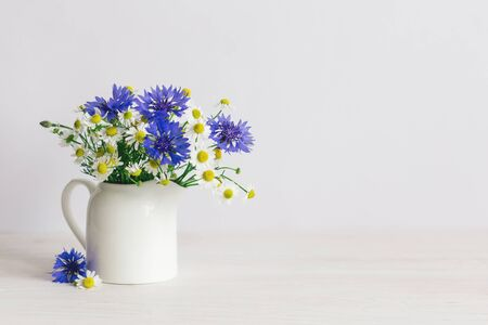 Romantic bouquet of the meadow flowers in a jar on a white background.  Chamomiles and Cornflower in a jar. Place for text.