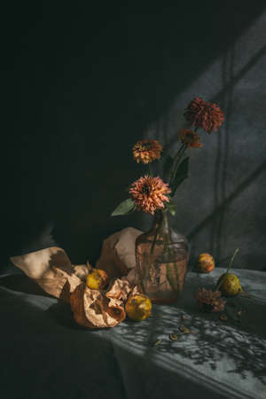 Still life with ripe pears and autumn flowers on a dark rustic background in a sunlights. Autumn background.