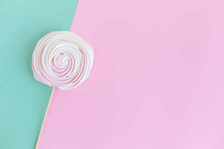Tasty meringue on pink and turquoise background. Concept for holiday greeting card or background. Flat lay. Place for text. Stock Photo