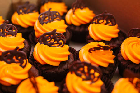 Tasty chocolate cupcakes with orange cream, decorated with chocolate pumpkins. Sweets for the celebration of Halloween.