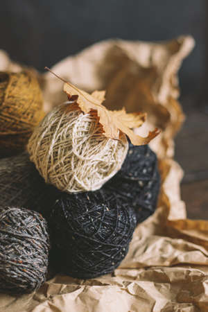 Cozy balls of yarn for hand knitting with dry oak leaf on a dark background. Autumn background for handmade and slow homelife. Selective focus.