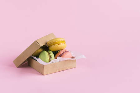 Set of tasty french macarons in a boxbon a pink pastel background. Place for text.