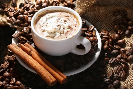 cup of coffee with cream and cinnamon on the textural fabrics