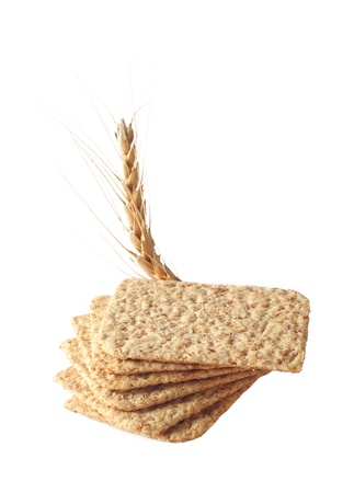 Stack of slices crispbread with spikelet wheat isolated on white Stock Photo