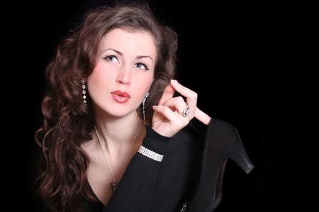 beautiful elegant woman holding a finger shoes