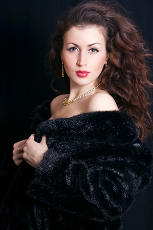 beautiful young woman in a black fur coat and jewelry photo
